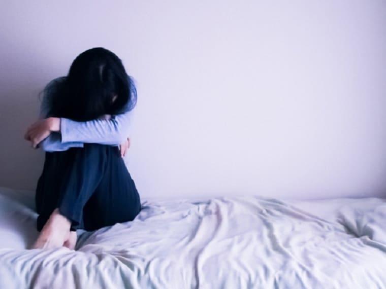 ベッドで膝を抱えてふさぎこむ女性