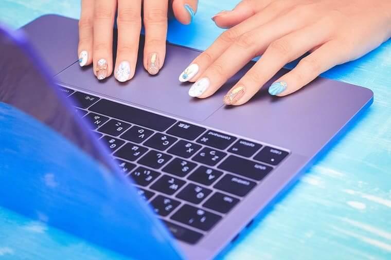 ノートパソコンを触る女性