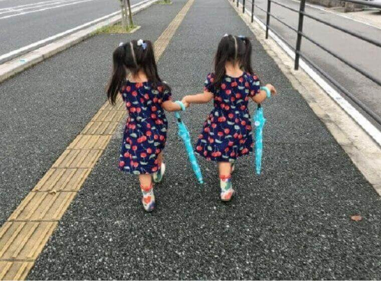 傘を持つ後ろ姿の女の子の双子