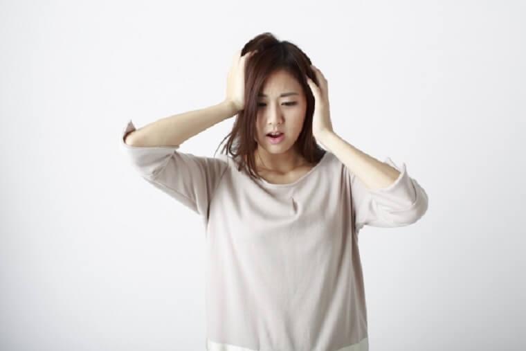 両手で頭を抱えて髪をつかむ女性