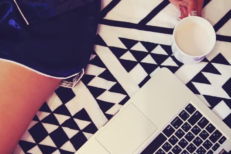 ノートパソコンの横でホットミルクを飲む女性