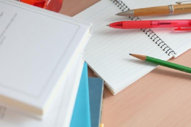 積み上げられた書籍とメモ長と鉛筆