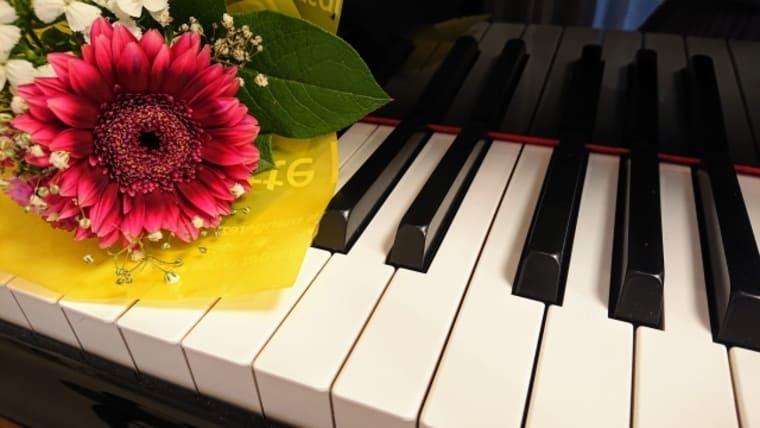 鍵盤に花が置かれたピアノ