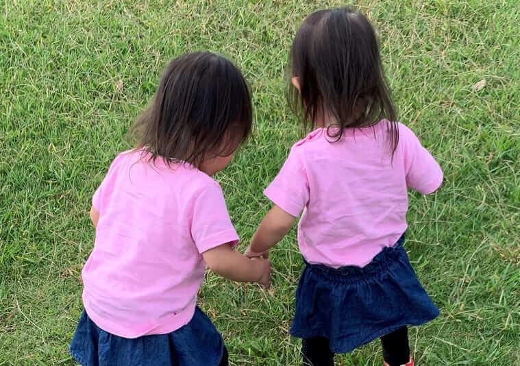 バッタを見つめる双子姉妹