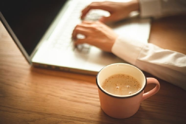 コーヒーを飲みながらパソコンをする女性