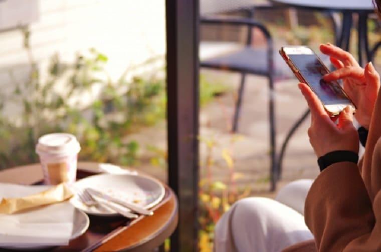 カフェでスマホを触る女性