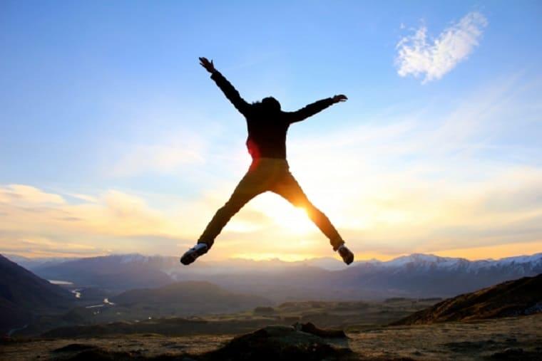 広大な風景を前にしてジャンプする男性